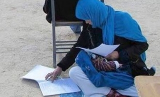 Inspiring photo of a woman writing exam while nursing her baby